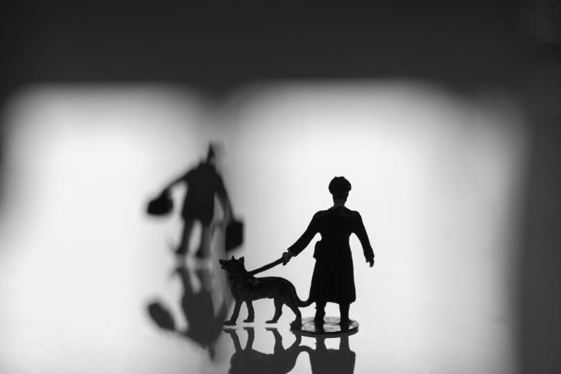 RESISTENCE II zeigt die Silhouetten des Miniatur-Wachmanns mit Schäferhund, der einem Reisenden mit Koffern entgegen steht.