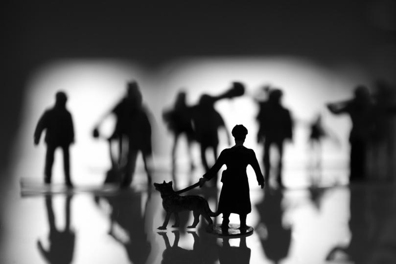 RESISTENCE III zeigt die Silhouetten einiger Menschen, die sich dem Wachmann mit Hund bedrohlich nähern.