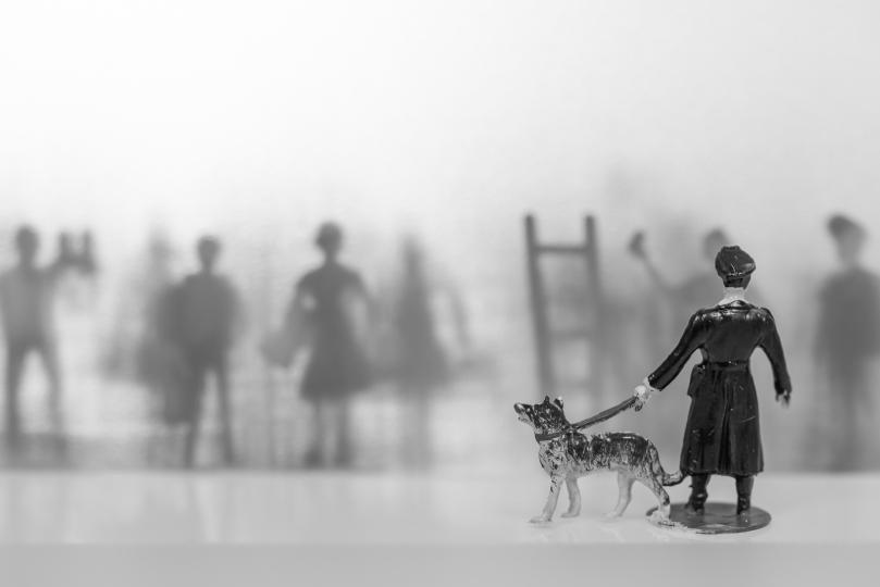 Die Silhouetten von Miniaturfiguren hinter einer Folie signalisieren einer davor stehenden Polizeifigur mit Hund, dass sie raus wollen.